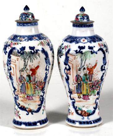 A pair of 19th century Chinese baluster vases decorated figures within panels, 26cm (10.25ins) high