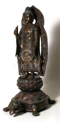 A Japanese bronze Buddha standing on a lotus flower mounted on a turtle, 47cm (18.5ins) high