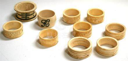 Four late 19th century Chinese Canton export carved ivory napkin rings, together with other napkin