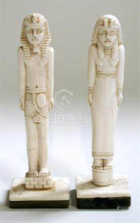 A pair of Egyptian carved bone figures standing on horn plinths, 14cm (5.5ins) high