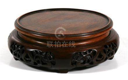 A large Chinese pierced and carved hardwood vase stand, 22cm (8.5ins) diameter