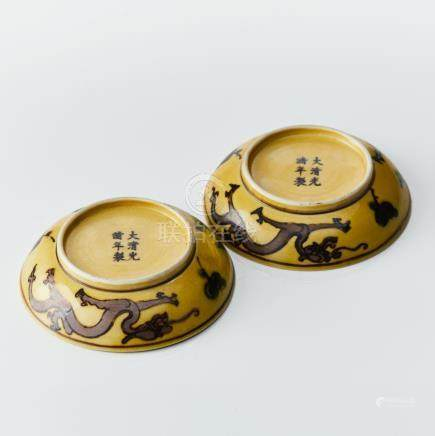 A pair of yellow-ground green and aubergine enamel 'dragon' dishes