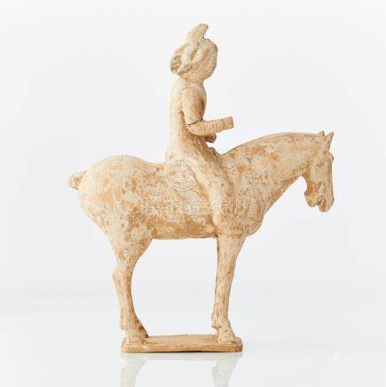 An unglazed pottery figure of a horse and female rider