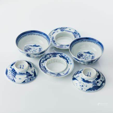 A pair of blue and white bowls, covers and stands