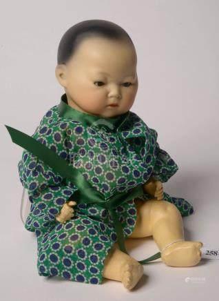 Rare petite poupée chinoise au corps en bois, à la tête en porcelaine et aux yeux amovibles.
