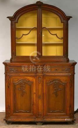 Meuble vitrine de style Louis XV en chêne sculpté muni d'une vitrine ouvrant par deux portes