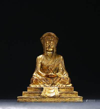 A gilt-bronze of seated guru