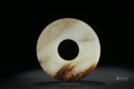 A white and russet jade carved 'mythical beast' disc