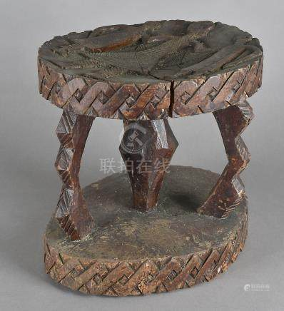A carved West African hardwood stool, on a three stem support united by an oval pedestal, the top