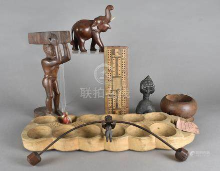 An ancient carved wooden African game, with twelve circular recesses, a balance toy, various
