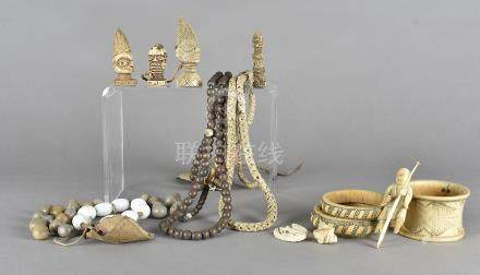 A collection of beads and charms, including a snake vertebrae, three late 19th Century ivory