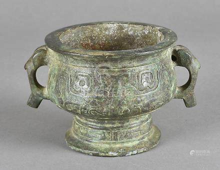 A 16th Century Chinese archaic shaped bronze twin handled footed bowl, 15 cm wide x 19 cm high