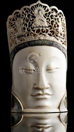 λ A Chinese carved ivory head of Guanyin, with a serene expression, wearing earrings and with a