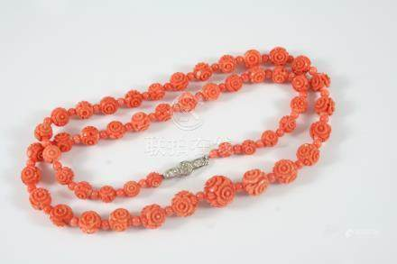 A SINGLE ROW GRADUATED CARVED CORAL NECKLACE formed with foliate carved coral beads alternately