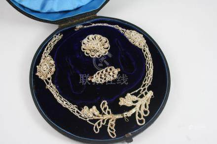 A VICTORIAN CASED SEED PEARL NECKLACE of foliate form, together with two brooches, all with some