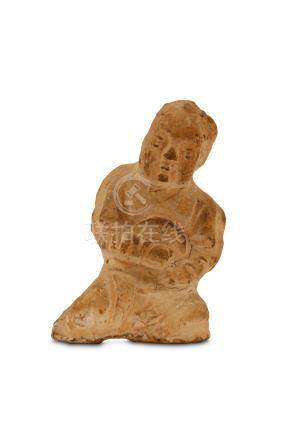 A Chinese pottery figure of a boy, Tang dynasty, modelled seated with the hands clasped to the