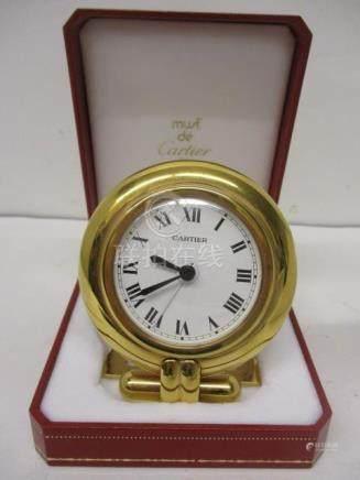 A Cartier quartz gilt metal cased, modern bedside clock having a circular case, white enamel dial