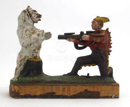 A cast iron money box modelled as a Native American Indian shooting a bear, h.