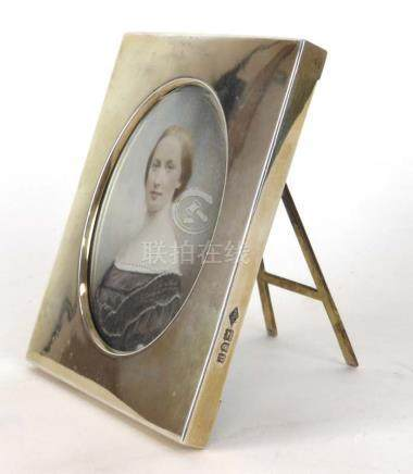 A late 19th century miniature head and shoulders watercolour within a silver photograph frame with
