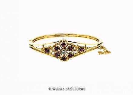 Ruby and diamond hinged bangle in 18ct yellow gold, central diamond with a surround of rubies in a