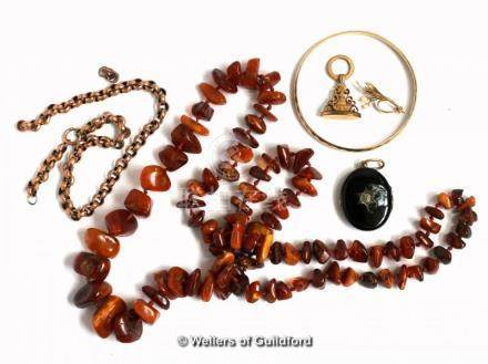 Selection of jewellery items, including a vintage amber bead necklace, locket, fob, and gold