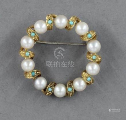 Broche ronde en or 18k à décor de perles de culture alternant avec des volutes serties de tu