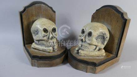 A Pair of Memento Mori Bookends Shaped Like Gravestones Mounted with Plaster Cast Human Skulls.