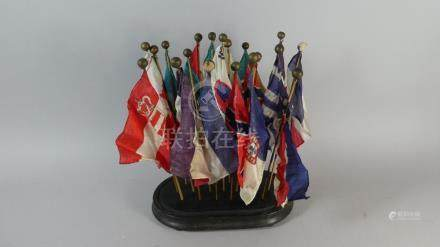 A Desk Top Display Nineteen Silk Nautical Flags Supported on Ebonised Wooden Plinth,