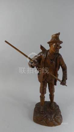 A Large Carved Black Forest Figure of Huntsman Carrying Deer and Holding Staff,