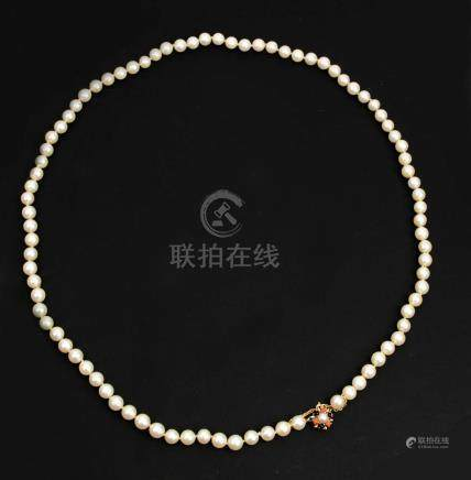 Cultured pearls necklace with a 18 k. yellow gold clasp with coral and onyx cabochons