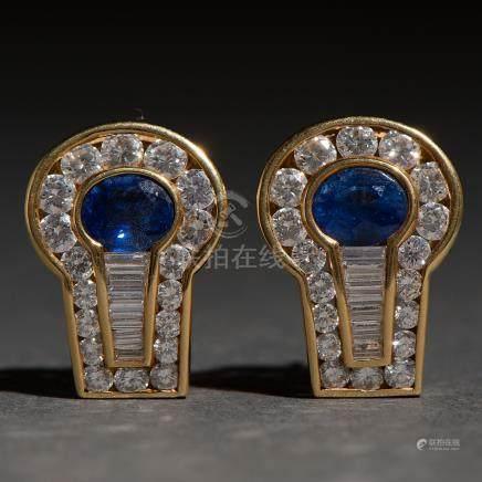Pendientes en oro amarillo de 18 kt. con zafiro central orlados por diamantes talla brillante y talla baguette.
