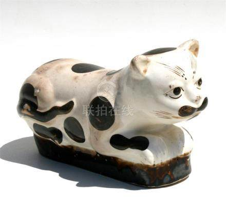 A Chinese pottery neck rest in the form of a recumbent cat, 35.5cms (14ins) long.