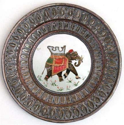 An Indian copper dish with central enamel roundel decorated with an elephant, 16cms (6.25ins) wide.