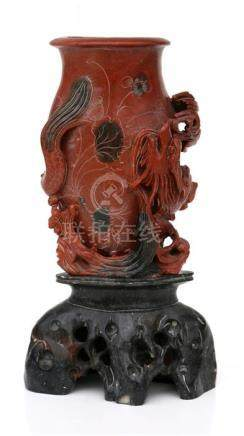 A Chinese rouge soapstone vase on stand carved with a dragon, 24cms (9.5ins) high.