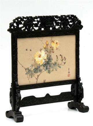 An Oriental carved wooden table screen with painted silk panel depicting bees and flowering