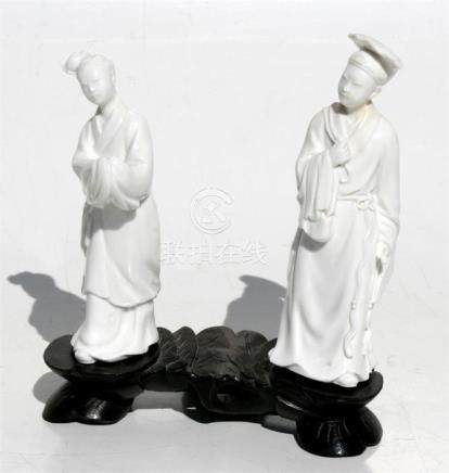 A pair of Chinese blanc de chine figures mounted on a carved hardwood stand, the largest figure
