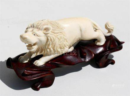 An early 20th century Japanese ivory carving in the form of a male lion, mounted on a carved