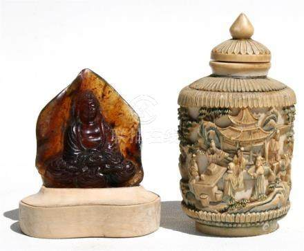A Chinese amber carving depicting a seated Buddha wearing flowing robes, 7cms (2.25ins) high;