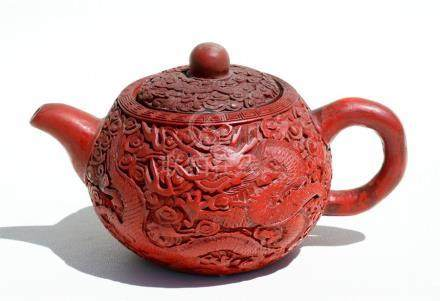 A Chinese cinnabar lacquer teapot decorated with scrolling dragons on a Yixing pottery body,