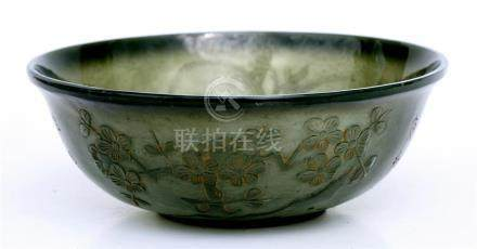 A Chinese spinach jade bowl decorated with prunus & calligraphy, with four-character seal mark to