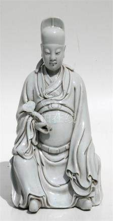 A Chinese blanc de chine style figure of a seated scholar wearing long flowing robes and holding a