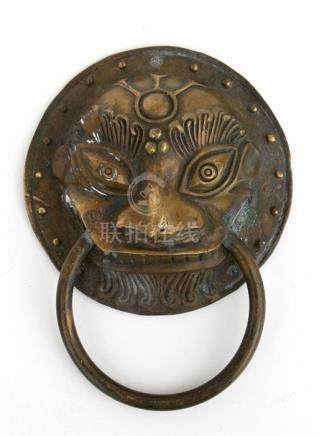 A Chinese bronze lion mask handle or door knocker, 13cms (5ins) diameter.