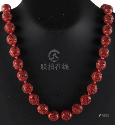 Property of a lady - a Chinese cinnabar lacquer bead necklace, the thirty-five individually