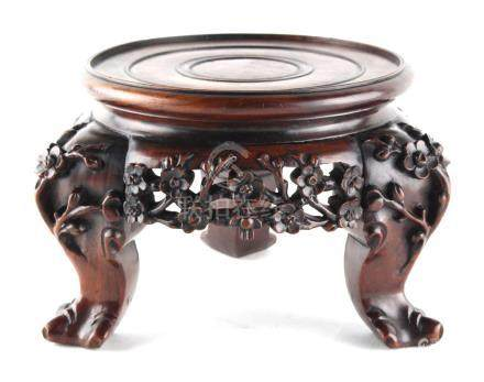A late 19th / early 20th century Chinese hongmu tripod stand, the frieze & legs profusely carved &