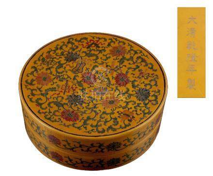 A Chinese yellow lacquer circular box & cover, with incised & painted decoration depicting scrolling