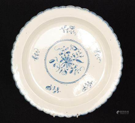 A 19th Century scalloped edge charger decorated in blue and white with a spray of flowers to the