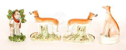 A pair of 19th Century Staffordshire sporting hounds each stood with their catch at their feet,