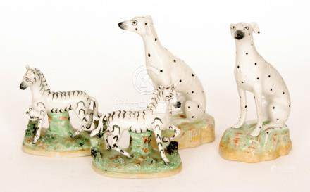 A pair of 19th Century Staffordshire models of Dalmatian hounds sat on naturalistic bases,