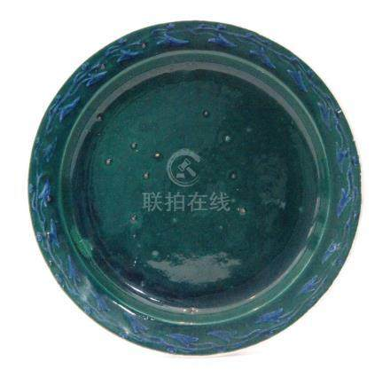 A Ruskin Pottery souffle glaze plate decorated in a blue green glaze with a hand painted border