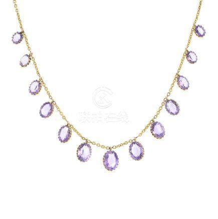 An early 20th century gold amethyst necklace. The graduated oval-shape amethyst collets, suspended